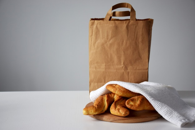 Juste des petits pains cuits sous une serviette de cuisine blanche sur une planche à découper en bois et un paquet de papier pour le service de livraison