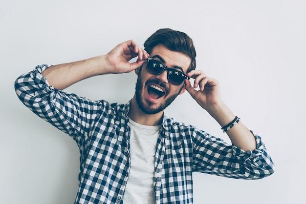 Juste pour le fun. beau jeune homme ajustant ses lunettes de soleil et faisant une grimace