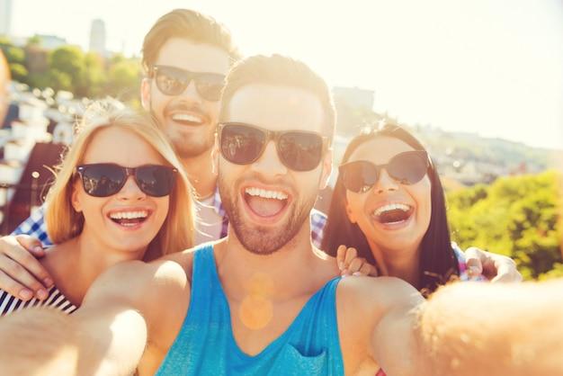 Juste pour le fun. groupe de jeunes joyeux qui se lient les uns aux autres et fabriquent une caméra selfieon tout en s'amusant sur le toit