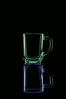 Juste un verre sur fond noir avec un reflet. couleurs vertes et bleues. isolé.