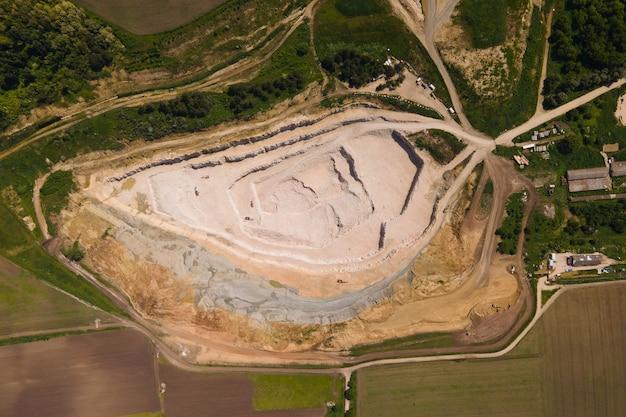 K vue aérienne industrielle de carrière minière à ciel ouvert avec beaucoup de machines au travail vue d'en haut extraction de sable de pierre blanche
