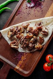 Kabab de viande servi avec épine-vinette et oignon