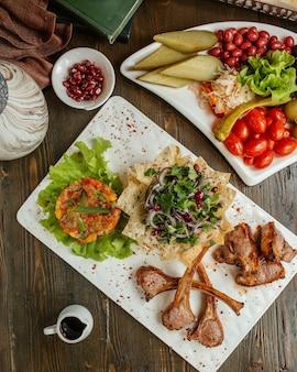 Kabab de viande servi avec salade de mangue, oignons, légumes verts et cornichons