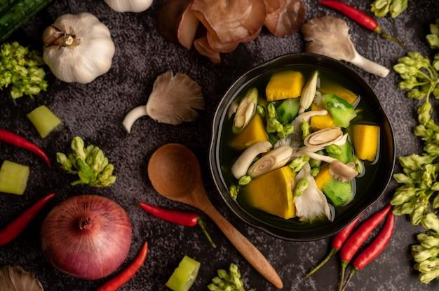 Kaeng liang dans un bol d'épices sur un sol en ciment noir.