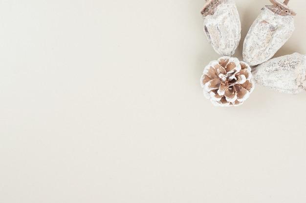 Kaki séché et pomme de pin sur une surface beige