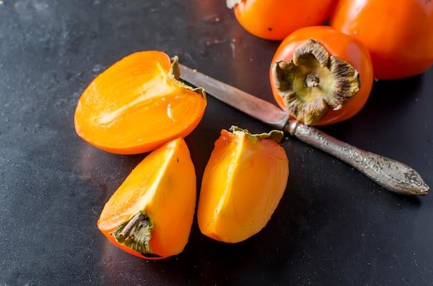 Kakis orange mûr sur le fond noir