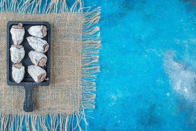 Kakis séchés sur une planche sur la texture, sur la table bleue.