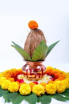 Kalash en cuivre avec noix de coco, feuille et décoration florale sur fond blanc