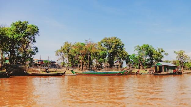 Kampong phluk sur village de pêcheurs flottant du lac tonle sap pendant la saison de sécheresse, maisons sur pilotis, personnes et bateaux