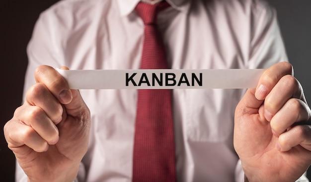 Kanban ou méthode maigre dans le mot de concept de gestion sur le papier dans des mains d'homme d'affaires