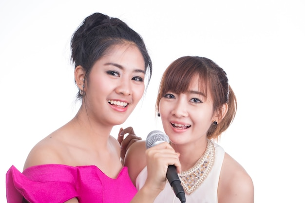 Karaoké, jeune fille tenant un microphone pour chanter et s'amuser avec sa musique sur fond blanc.