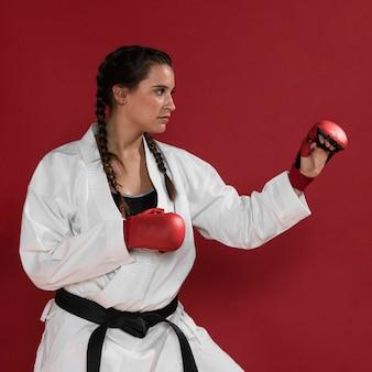 Karaté femme en action isolée sur fond rouge