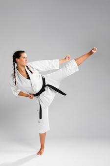 Karaté femme sur le côté en kimono blanc traditionnel sur fond blanc