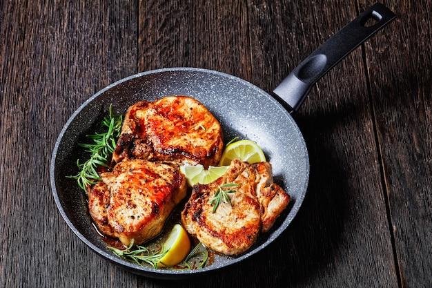 Karbonade de porc rôti, escalopes de porc avec brins de romarin et tranches de citron dans une poêle sur une table en bois, vue horizontale d'en haut