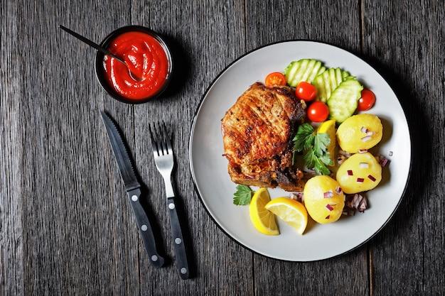 Karbonade de porc rôti, escalopes de porc avec pomme de terre bouillie et concombre et citron tranchés sur une assiette sur une table en bois, vue horizontale d'en haut