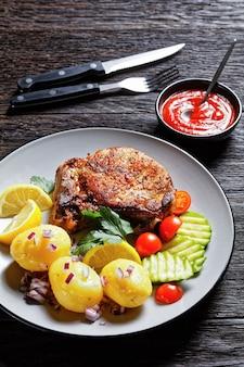 Karbonade de porc rôti, escalopes de porc avec pomme de terre bouillie et concombre et citron tranchés sur une assiette sur une table en bois, vue verticale d'en haut
