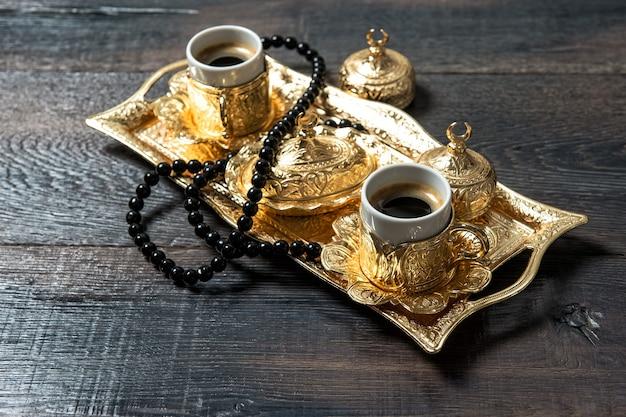 Kareem ramadan. tasses à café, décorations dorées et chapelet