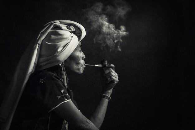 Karen femme tribale fumant de l'opium avec une pipe près de chiangmai, thaïlande.