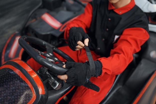 Kart racer en uniforme rouge met des gants, karting auto sport indoor. course de vitesse sur piste de karting étroite avec barrière de pneu. compétition de véhicules rapides, passe-temps à haute adrénaline