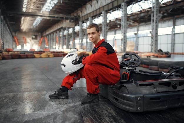 Kart racer en uniforme rouge pose avec hemet dans les mains, karting auto sport indoor. course de vitesse sur piste de karting étroite avec barrière de pneu. compétition de véhicules rapides, passe-temps à haute adrénaline