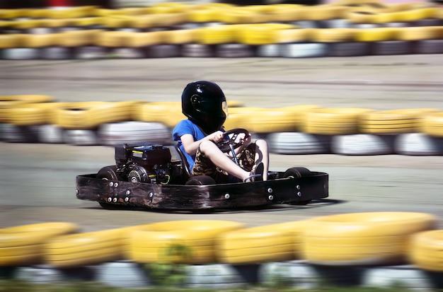 Karting - pilote en casque sur circuit de karting. arrière-plan flou de mouvement pour indiquer la vitesse