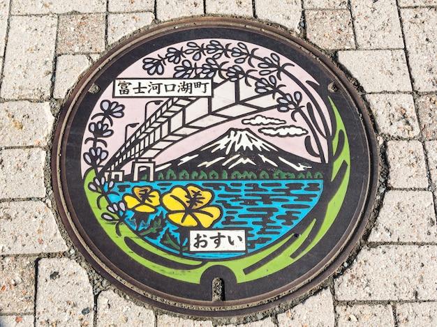 Kawaguchiko, japon - 24 octobre 2015: mt. fuji, le pont et le lac sur la plaque d'égout du lac kawaguchiko à yamanashi.