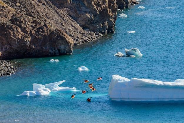 Kayak dans la mer arctique près de l'iceberg