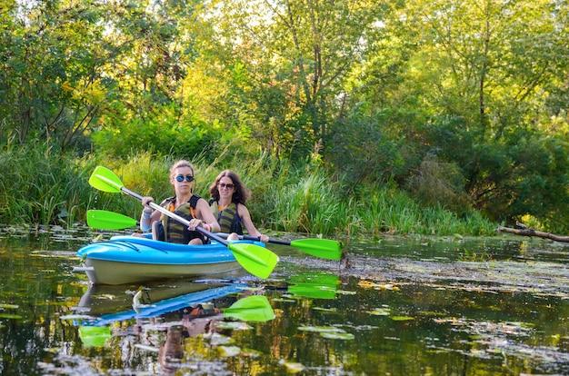 Kayak en famille, mère et fille pagayant en kayak sur la rivière en canoë, s'amuser, week-end d'automne actif et vacances avec enfants, concept de remise en forme