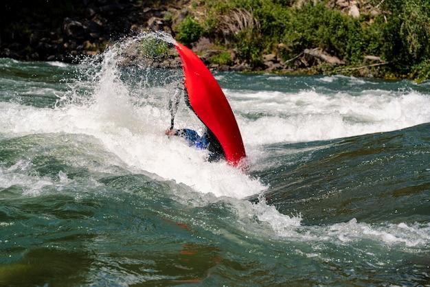 Kayak freestile homme concurrent complétant la manœuvre à 360 degrés