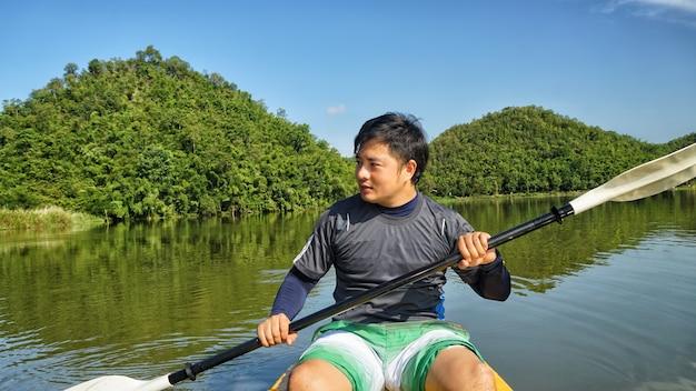 Kayak homme pagayant un kayak. concept d'aventure, de voyage, d'action, de style de vie