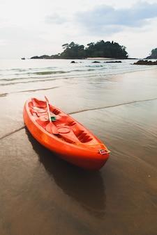 Kayak rouge à la plage au coucher du soleil.