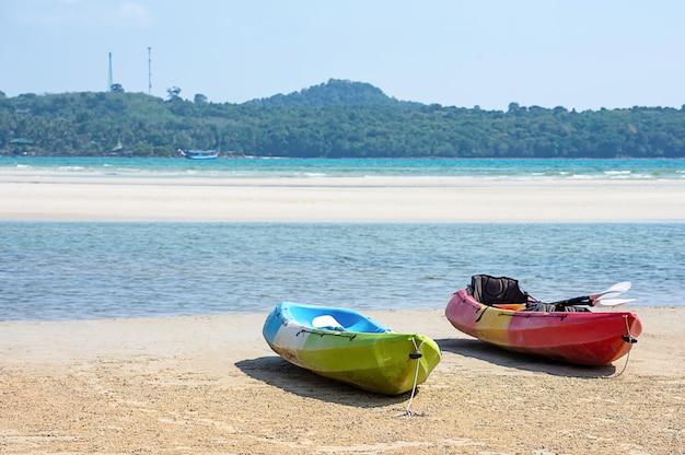 Kayak sur le sable de la mer, fond de montagnes et de rochers.