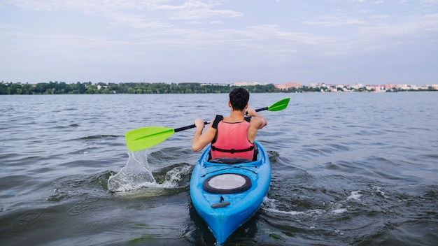 Kayaker éclaboussant l'eau avec une pagaie en kayak