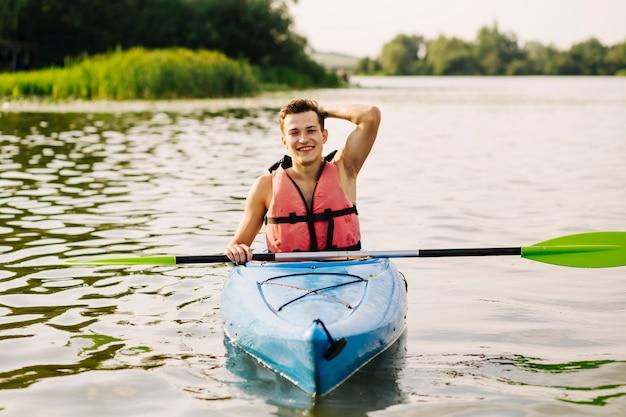 Kayakiste mâle flottant en kayak sur le lac idyllique