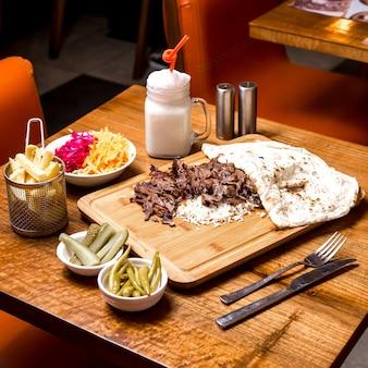 Kebab d'agneau servi sur du riz avec des cornichons de pain plat ayran et frites