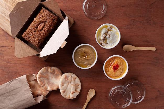 Kebab au four avec accompagnements, houmous, babaganoush, caillé et pain pita. nourriture arabe. emballage de livraison. vue de dessus