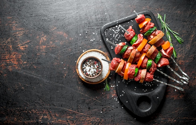 Kebab de boeuf cru avec des légumes et des épices dans un bol. sur une surface rustique sombre