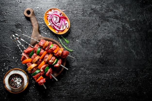 Kebab cru sur une planche à découper avec des oignons émincés et des épices dans des bols. sur une surface rustique noire