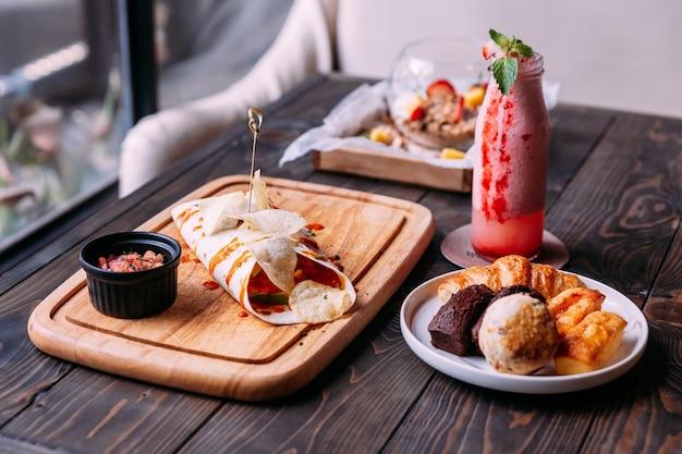 Kebab avec des frites, des produits de boulangerie frais, y compris scone, financier et smoothie aux fraises.
