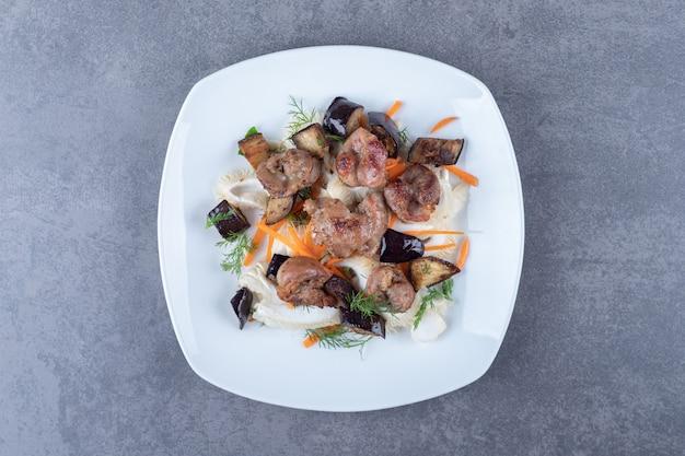 Kebab grillé savoureux sur plaque blanche.