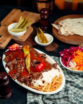 Kebab iskender garni de sauce tomate, servi avec pomme de terre et yaourt