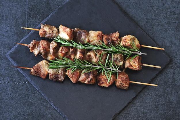 Kebab juteux au romarin sur une planche de pierre sombre.