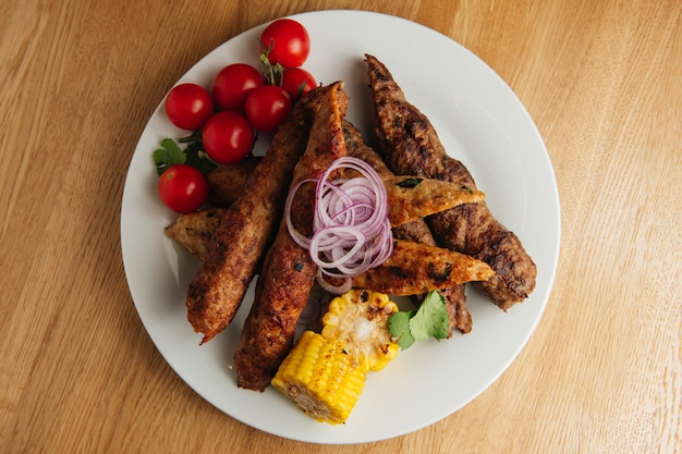 Kebab lula avec du pain pita sur plaque blanche