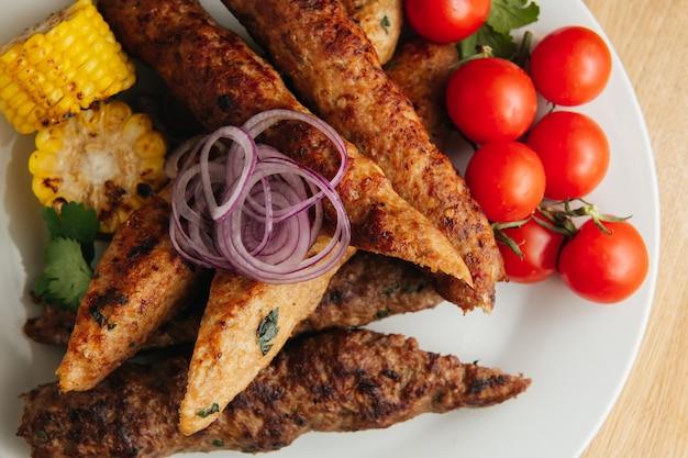 Kebab de lula avec pain pita aux tomates cerises, oignons et maïs