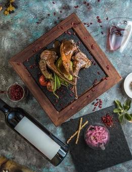 Kebab d'os d'agneau avec une bouteille de vin rouge