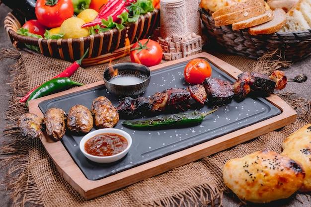 Kebab de viande sur planche de bois poivron pomme de terre tomate adjika