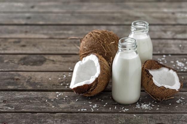 Kéfir de noix de coco en bouteilles sur table en bois. boisson végétalienne non laitière saine ou fermentée. concept d'alimentation saine