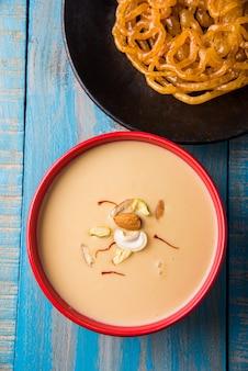 Kesari jalebi ou jilbi avec rabdi est une délicieuse recette indienne servie comme dessert dans les festivals ou les mariages. servi dans une assiette et un bol sur fond coloré ou en bois. mise au point sélective