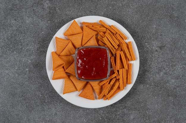Ketchup, chips de maïs et pain séché sur plaque sur la surface en marbre