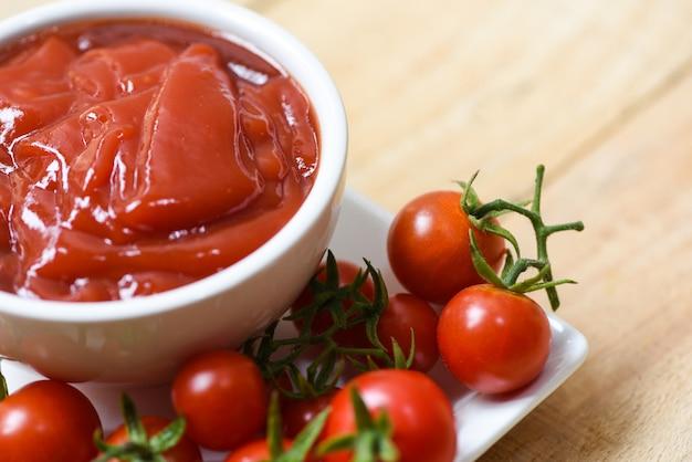 Ketchup dans une tasse et tomates fraîches sur une assiette